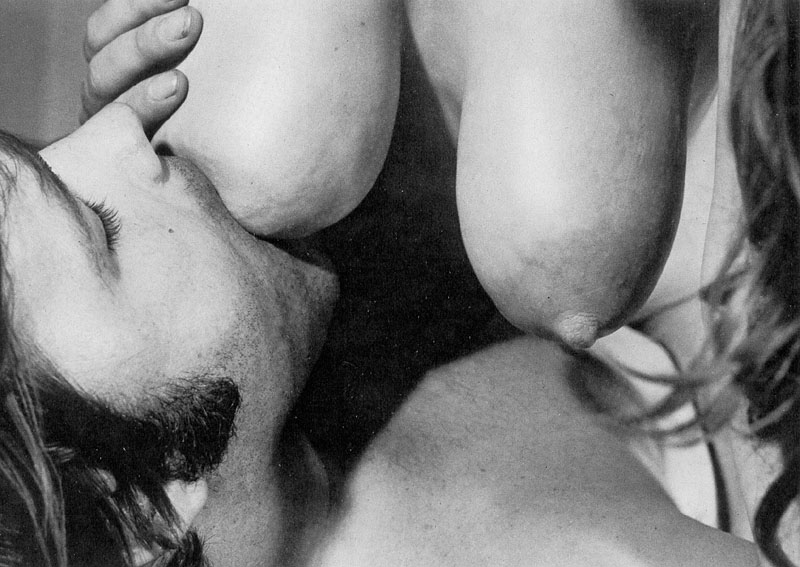 a pair of milk-filled breasts capped with darkened and enlarged teats being nursed by a man who is hungry for their milk