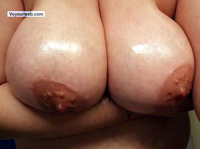 milk engorged breasts capped by large, dark, bumpy areolas